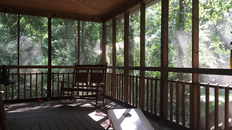 Image of the porch of a cabin with a rocking chair and cornhole board  at Suwannee River State Park.