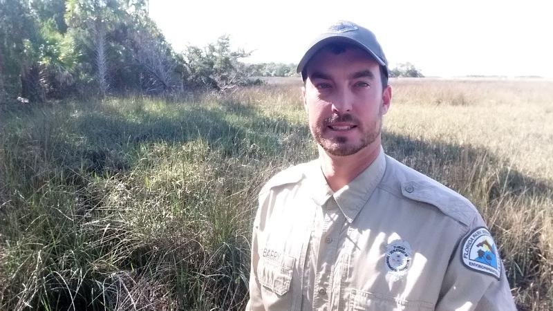 A man in uniform stands in front of a scrub habitat.