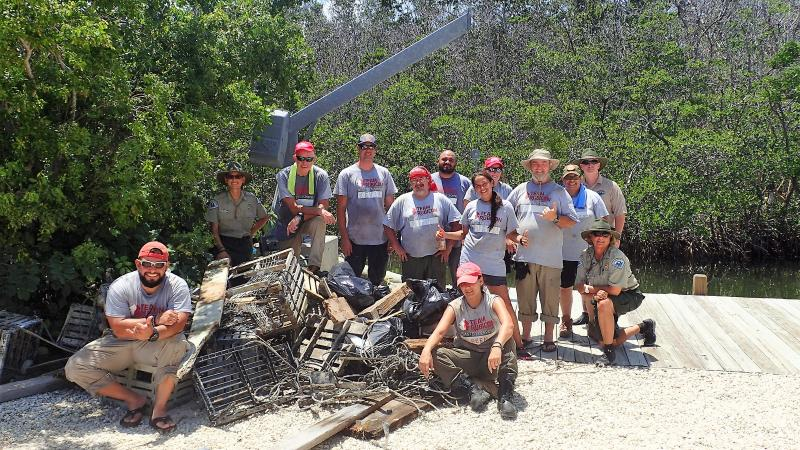 Group poses on dock with the marine debris removed from the island