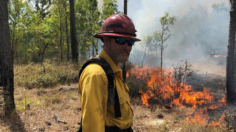 a man in protective gear stand sin front of a prescribed fire with a drip torch