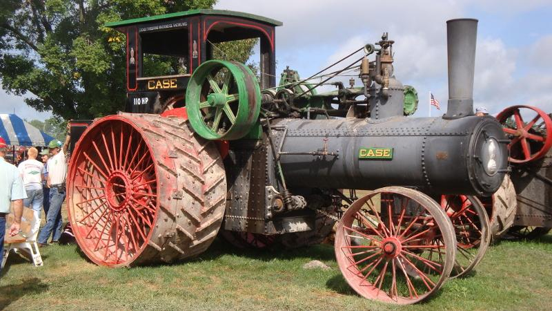 a large antique tractor with red wheels and a steam engine