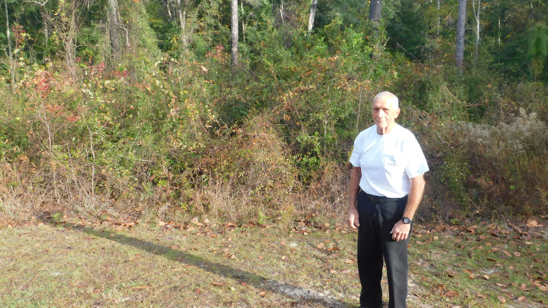 Volunteer Bill Cade stands beside as park trail, with hammock trees in the background.