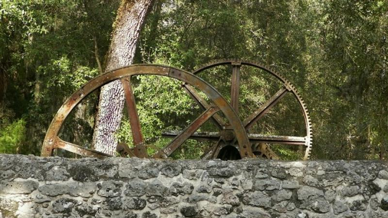 Two large metal rusted wheels above a gray stone wall.