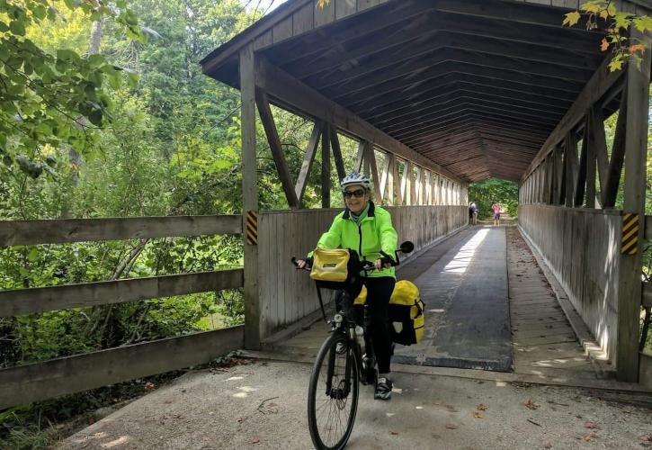A woman on a bicycle rides under a covered bridge.