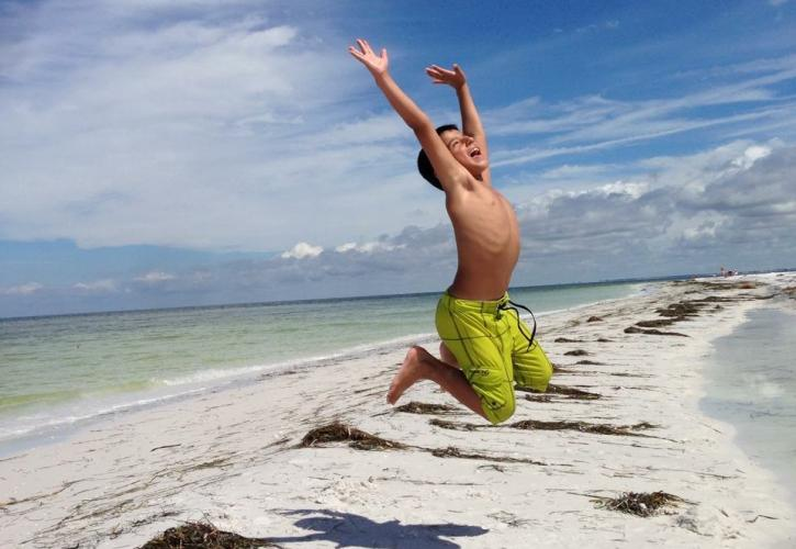 Kid Jumping on Beach