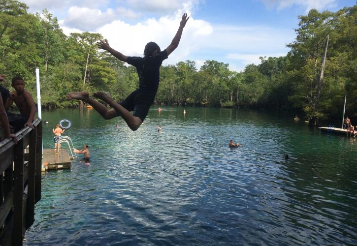 A boy jumping off the deck into the springs