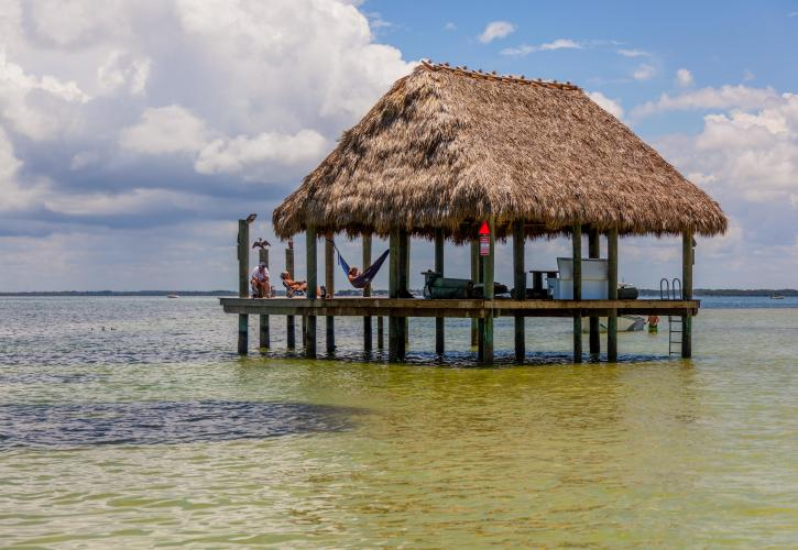 A view of a tiki style pavilion out in the middle of the water.