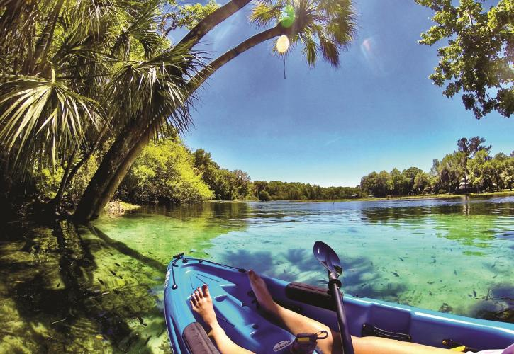 A view of the clear, blue water from the side of a kayak.