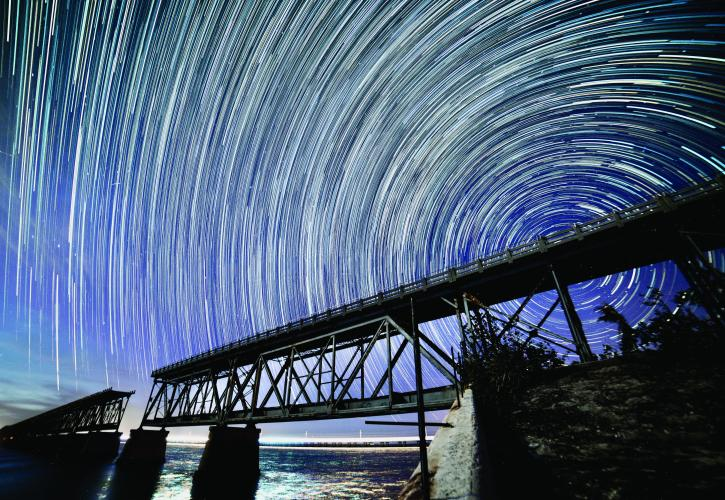 Time Lapse Photography Showing Star Circling The Bridge At Night