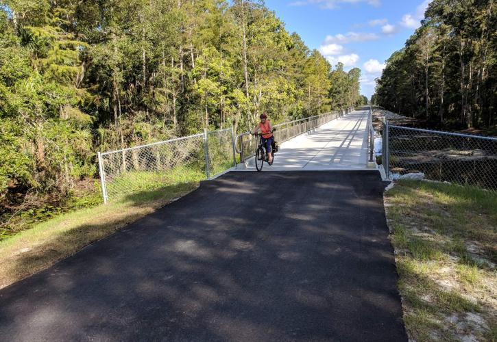 A person on a bicycle rides along a paved trail over a bridge.