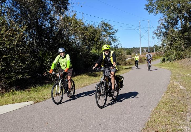 Three cyclists ride along a paved trail.