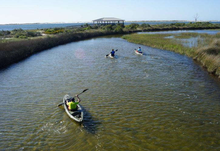 Three kayakers paddle around coastal marsh with view of Pavilion in the background.