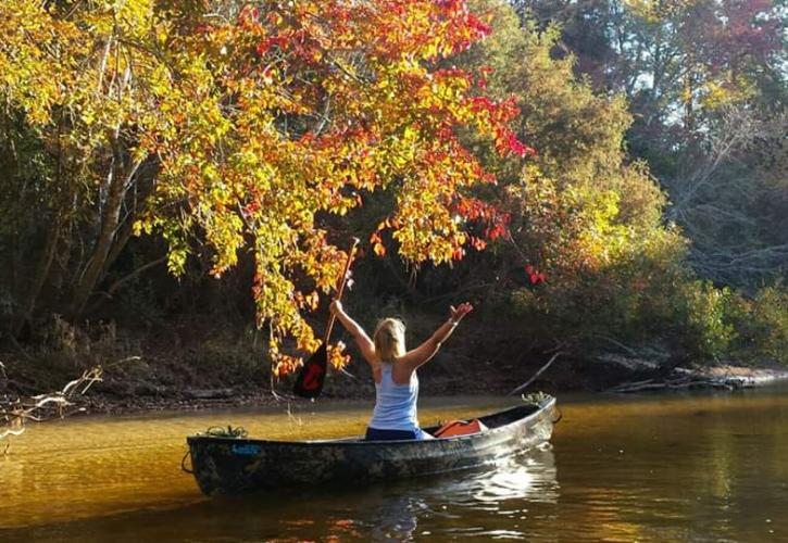 Woman in canoe throws arms up to embrace her surroundings. Fall foliage is a mix of vibrant yellows and oranges.