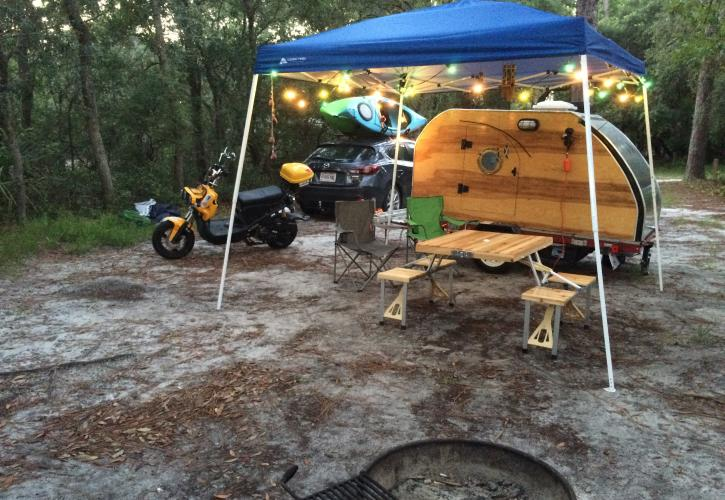 Tear drop camper set up under pop up tent next to motorcycle.