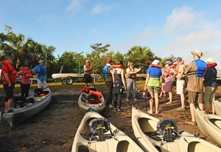 Group of people standing around canoes preparing for a paddling trip on the river.