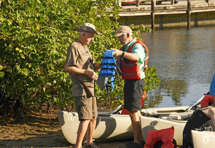 Two men preparing to canoe hold a life vest.