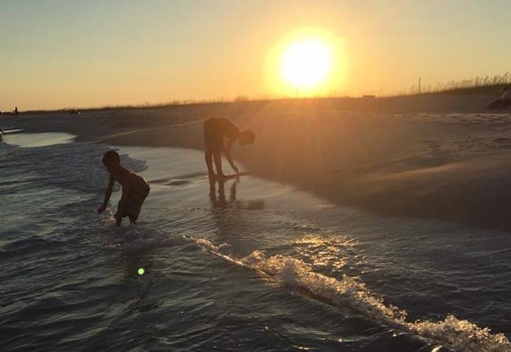 Two children play in the waves with setting sun in the background.