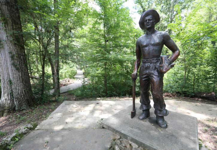 Statue on Civilian Conservation Corp member holding an ax in one hand.