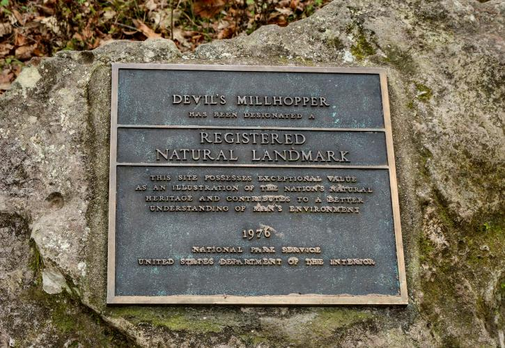 The plaque stating that Devil's Millhopper is a Natural National Landmark.
