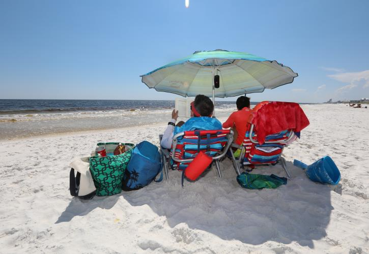 Couple sit under the shade of a beach umbrella reading a book.