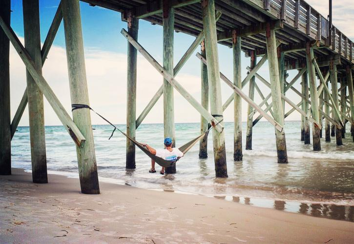 Man looks out at the water from hammock under the Gulf Pier.