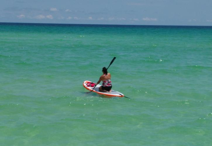 Paddle boarder glides through emerald green waters meeting clear blue skies.