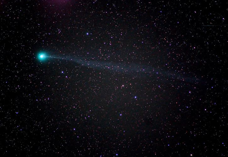 A bight blue comet flying across the night sky with stars surrounding it.