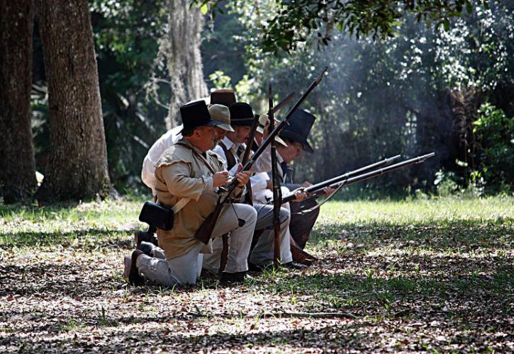 a line of men loads muskets while kneeling.