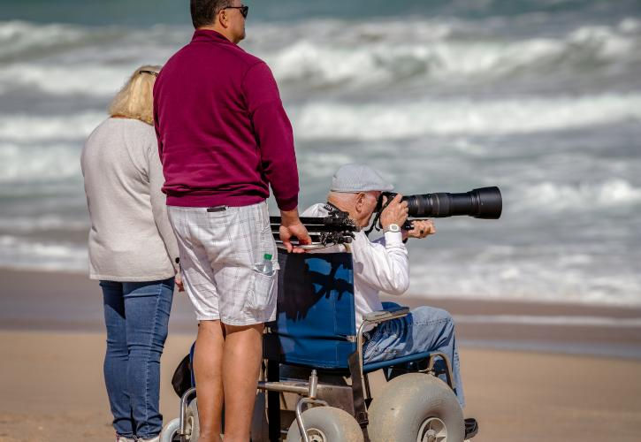 3 visitors on the beach and looking at water, older gentleman is in an all-terrain beach wheelchair taking a photograph