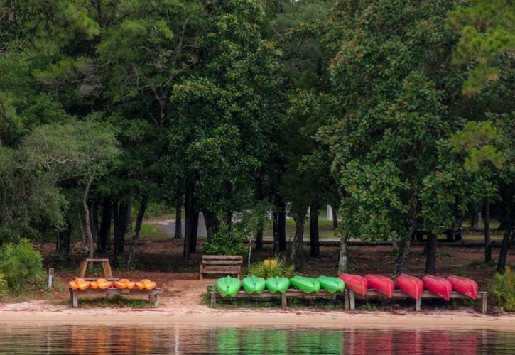Canoes and Kayaks are lined up on racks at the shoreline.