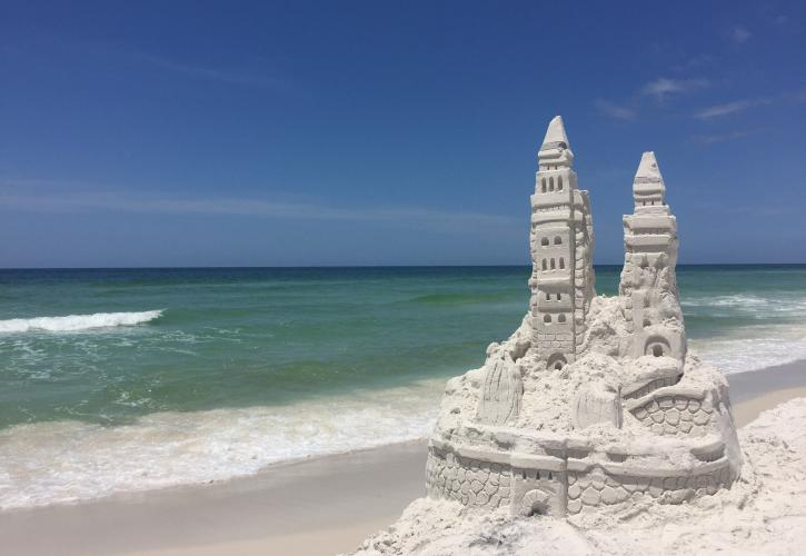 Sand castle with emerald green water in background.