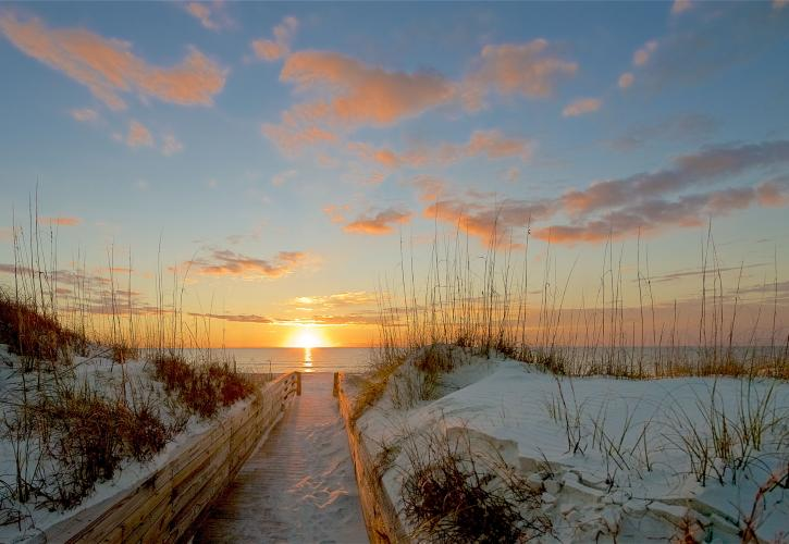 Boardwalk between white sand dunes leads to setting sun.