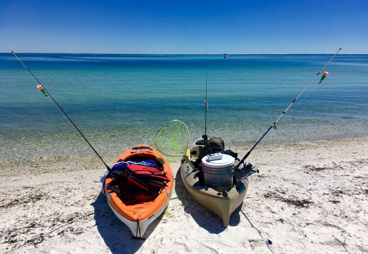 Two kayaks equipped with fishing poles sit on the white sandy beach at the edge of emerald green water.
