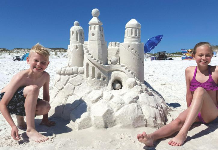 Kids smiling proud of the amazing sandcastle they built