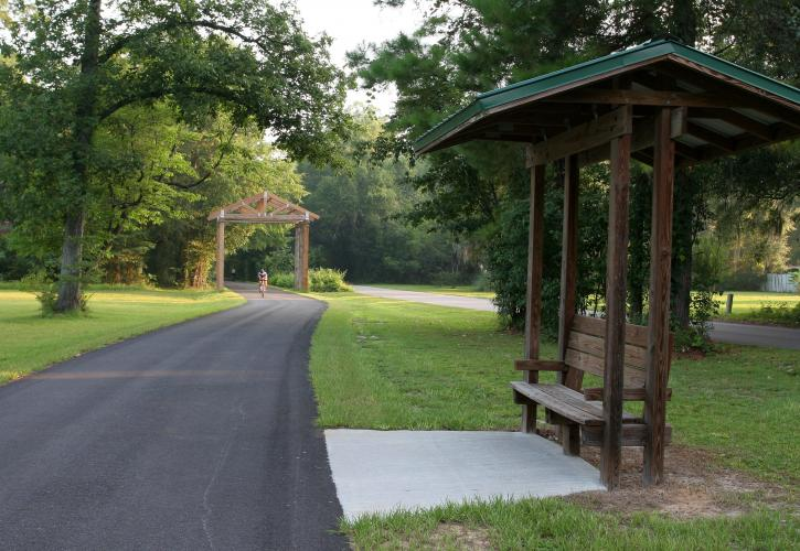 Paved path with bench under covered pavilion.