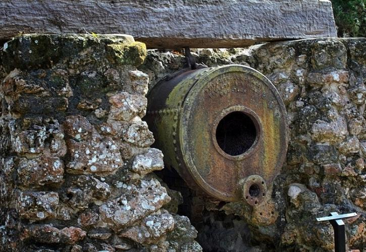 a rusted metal boiler set into a stone wall