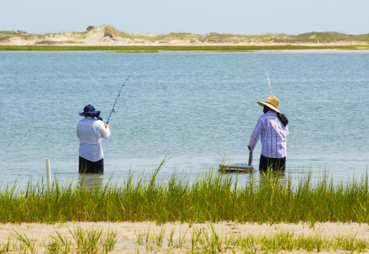 Two men fish in the water surrounded by sand dunes and marsh grasses
