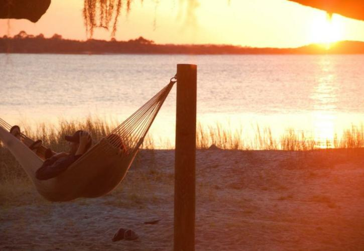 a hammock with two people in it hangs on a beach