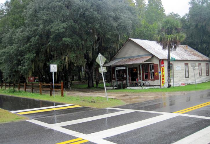 a small store sits on the intersection of a road and a paved bike path