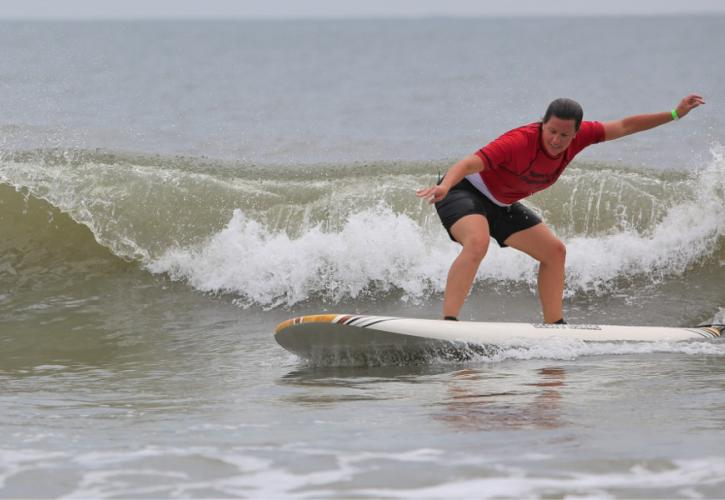 A woman in red is seen surfing off the beach of Little Talbot Island State Park