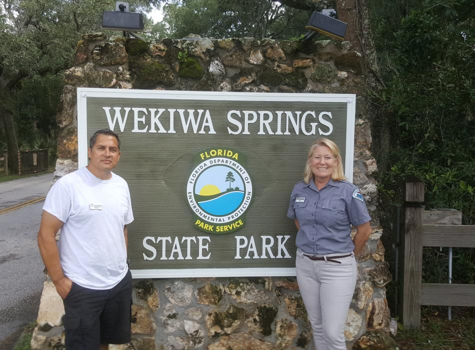 Volunteers Chris & Kim Aviles smiling with the Wekiwa Springs sign