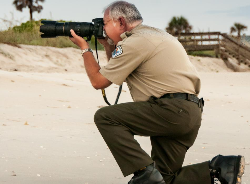 Ed, in his ranger uniform on the beach, taking photos.