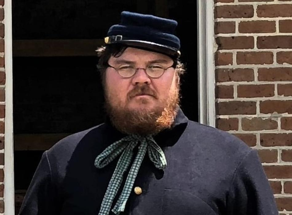 Andy, dressed as a Civil War Soldier, in front of a brick building.