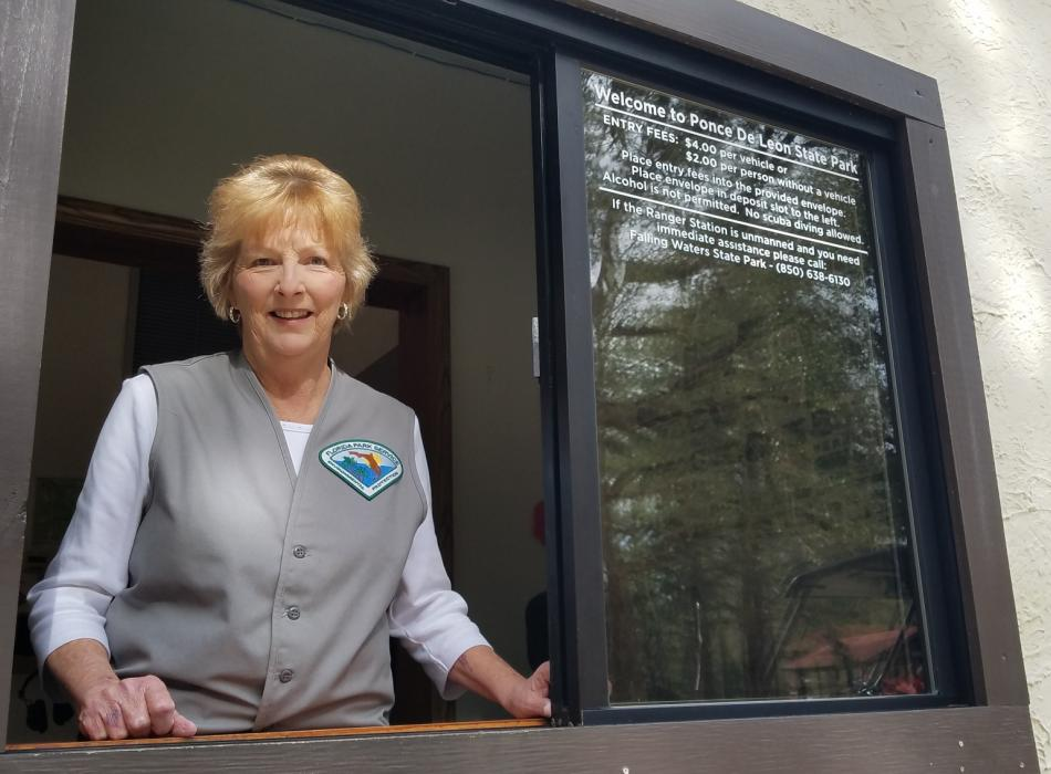 Volunteer Jerrettha French stands at the window of Ponce de Leon Springs Ranger Station ready to greet visitors with a smile.
