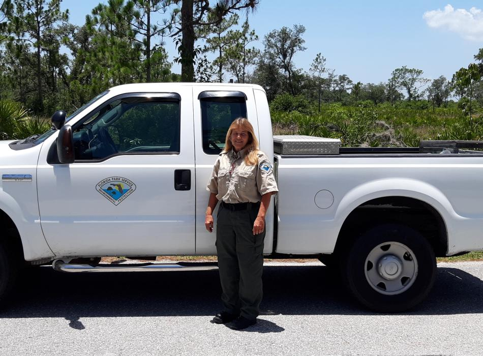 Lyndel Mclellen standing in front of a truck, wearing her ranger uniform and smiling at the camera.