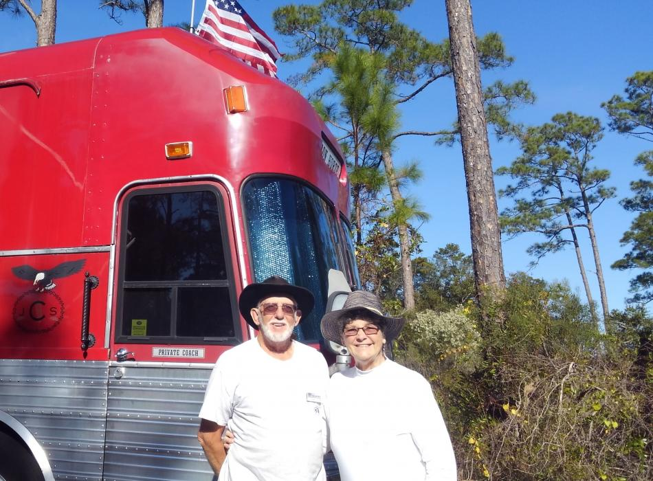 "Volunteers Jimmy and Sadie Clay standing in front of their red bus known as the ""Iron Horse""."