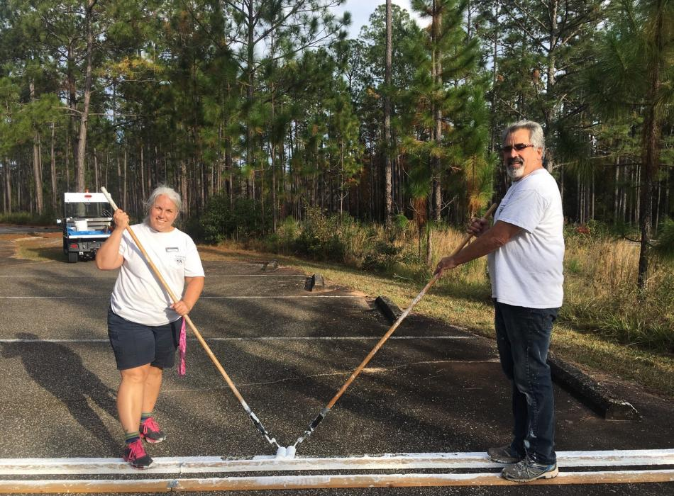 Man and woman hold paint rollers painting parking lot lines.
