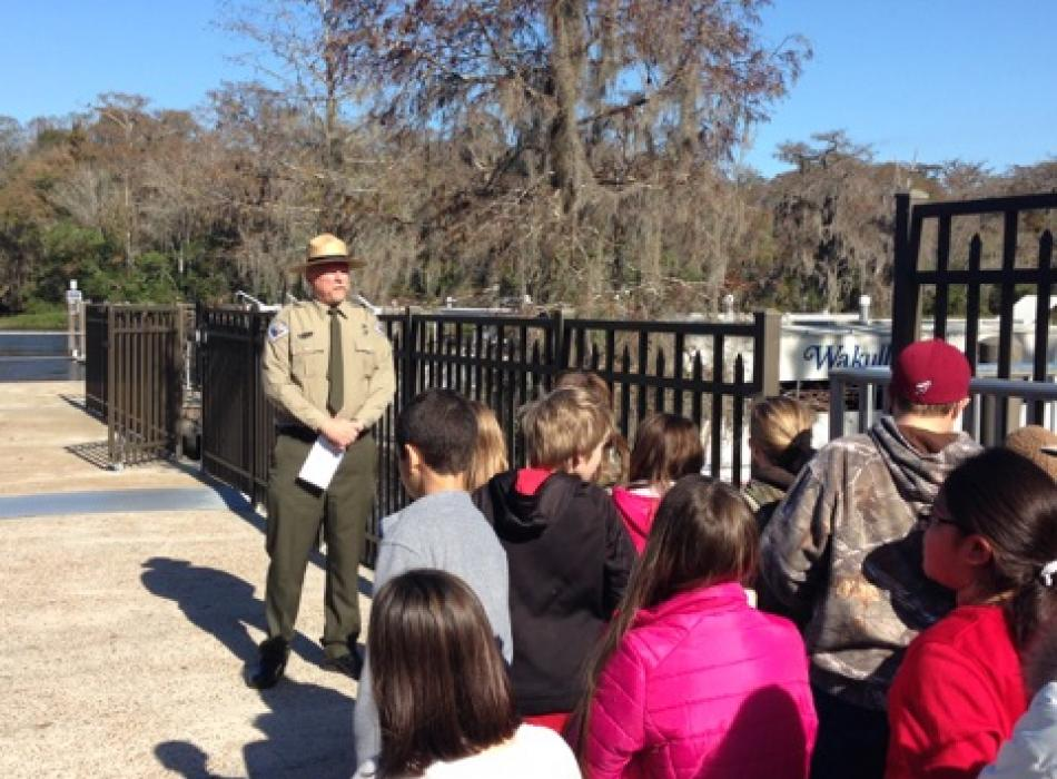 A group of children standing in a group, listening to a park ranger.