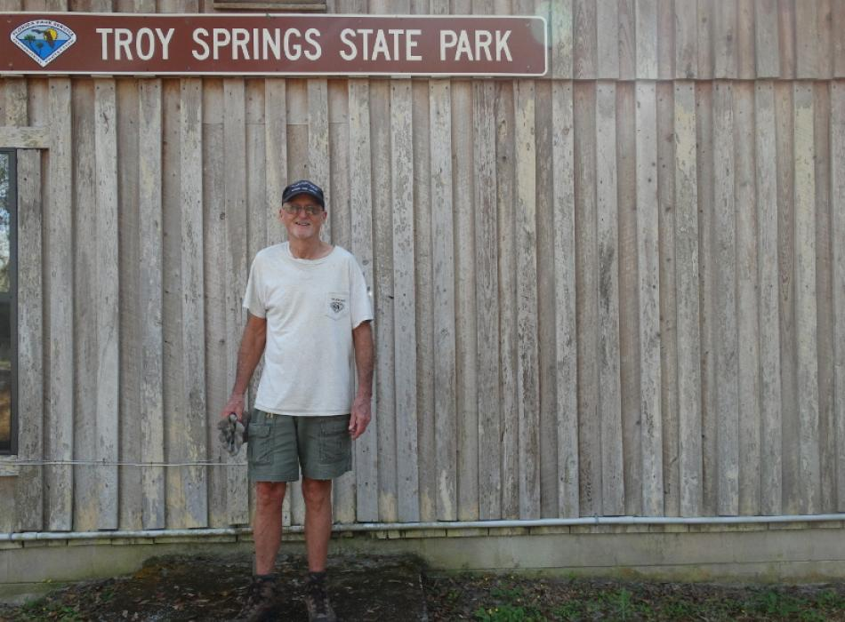"a man in work clothes stands against a wooden fence, below a sign reading ""Troy Springs State Park"""