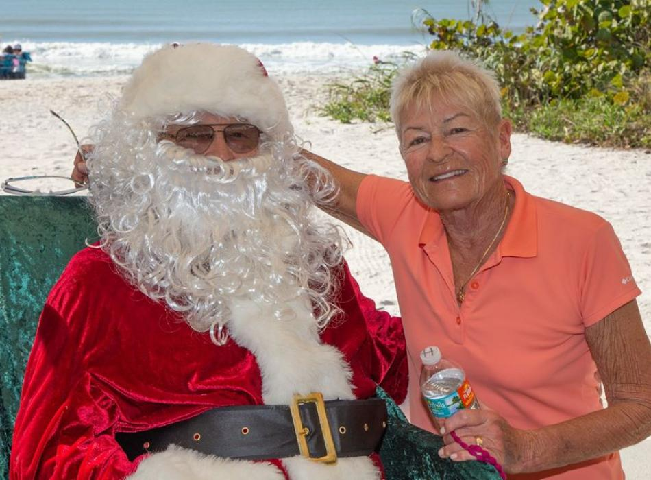 Ingrid Twiefel smiling at the camera, sitting next to her husband Richie dressed up as Santa for an event.
